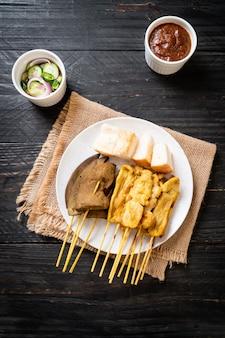 ピーナッツソースとキュウリのスライスと酢の玉ねぎであるピクルスのポークサテ