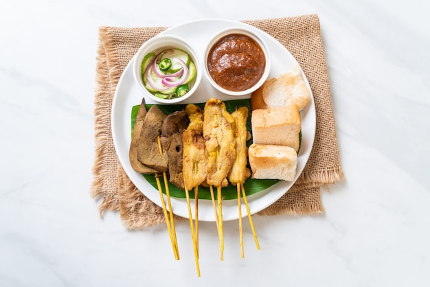 Pork satay with your peanut sauce  and pickles which are cucumber slices and onions in vinegar