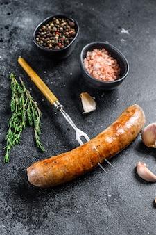 Сосиски из свинины на гриле со специями и зеленью на вилке для мяса