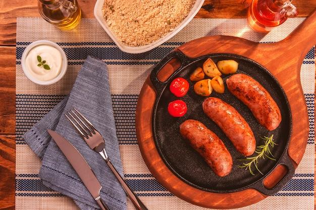 Pork sausage roasted in an iron frying pan