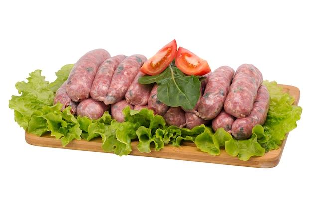 Свиная колбаса с рукколой на разделочной доске на белом фоне.