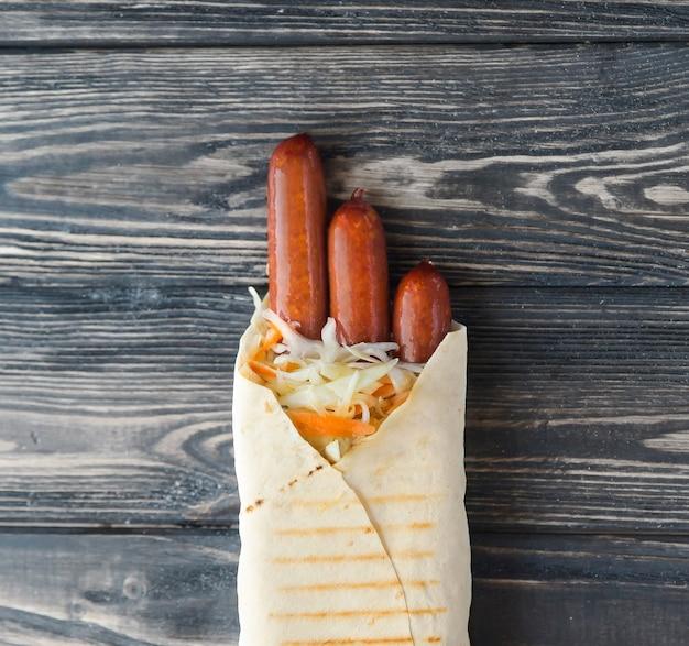 木製の背景にピタパンのポークソーセージ。コピースペース付きの写真。