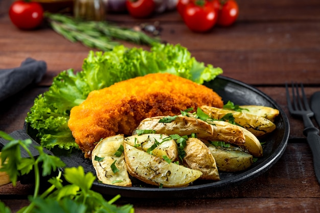 Pork schnitzel with baked potatoes in a pan on a wooden table