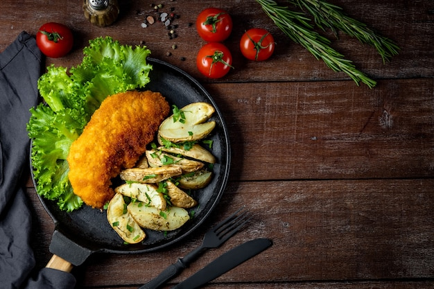 Pork schnitzel with baked potatoes in a pan