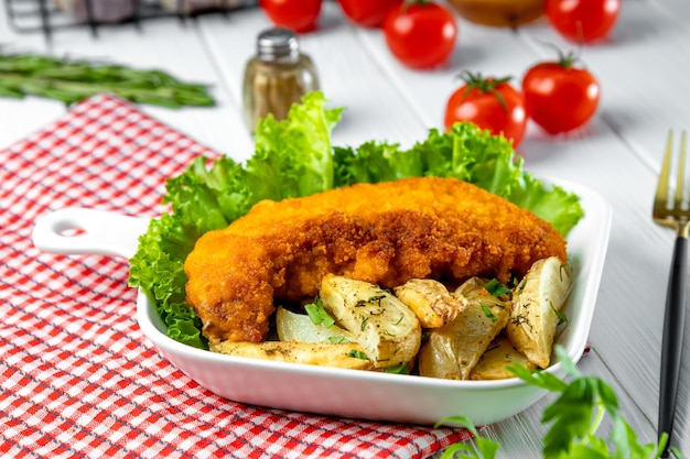 Pork schnitzel with baked potatoes on a white table