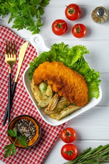 Pork schnitzel with baked potatoes on a white wooden