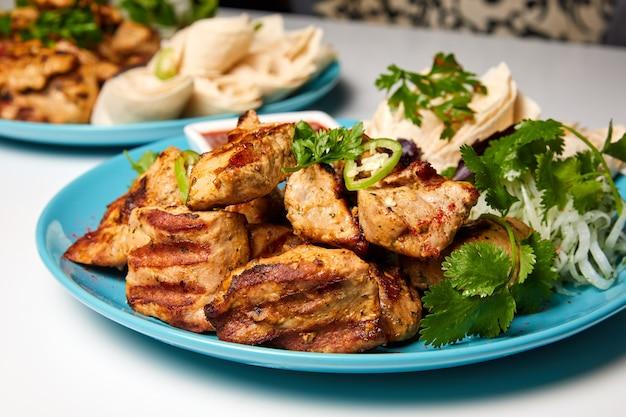 Шашлык из свинины или кебаб с лавашем, маринованным луком и красным соусом