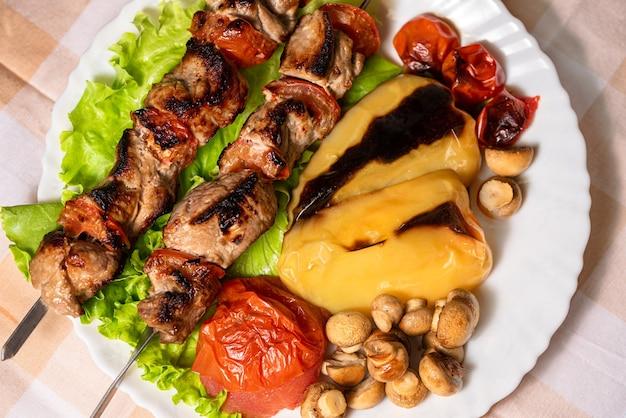 Шашлык из свинины с салатом и запеченными овощами на белой тарелке мясо гриль на шпажках