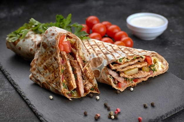 Pork shawarma, on a black background, with herbs, tomatoes and sauce