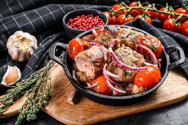 Шашлык из свинины с луком и помидорами на сковороде. мясо на гриле. черный фон. вид сверху.