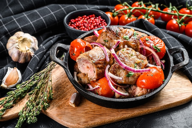 Pork shish kebab with onion and tomato in pan. grilled meat.  black background. top view.