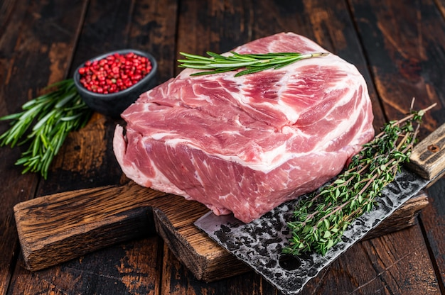 Pork shoulder raw meat for fresh steaks on wooden cutting board with butcher cleaver. dark wooden
