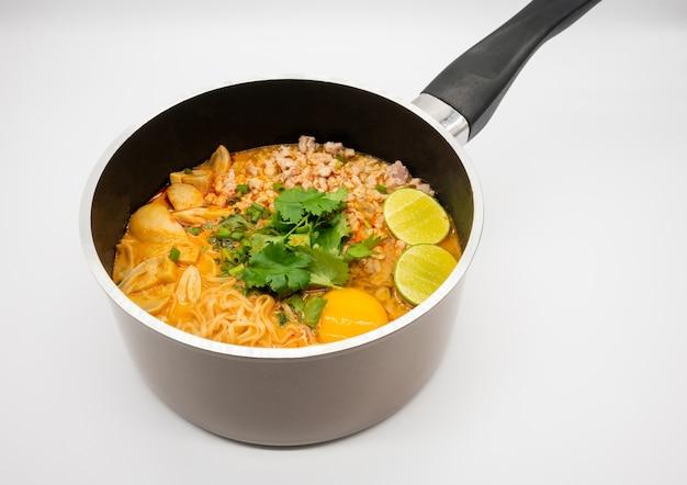 Острый свинины «том ям» с лапшой быстрого приготовления в горячем горшке, изолированном на белой поверхности. знаменитая тайская еда.