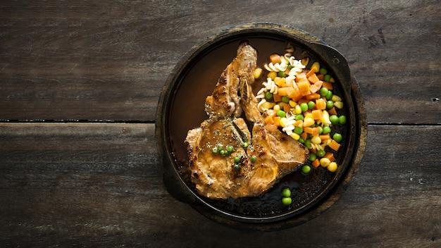 ポークステークは、木製のテーブルの上面から見たサヤインゲンのニンジンとトウモロコシとグレービーソースのホットパンで提供しています