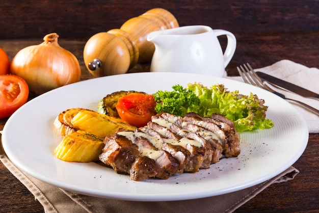 Pork steak grilled, baked potatoes and vegetable salad on wooden table.