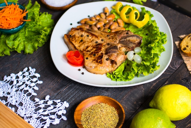Pork steak homemade cooking with spices leaves lettuce on wooden cutting board, and a dish,