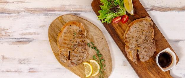 복사 공간이 있는 꼭대기에서 찍은 나무 접시에 레몬과 허브를 곁들인 돼지고기 스테이크.