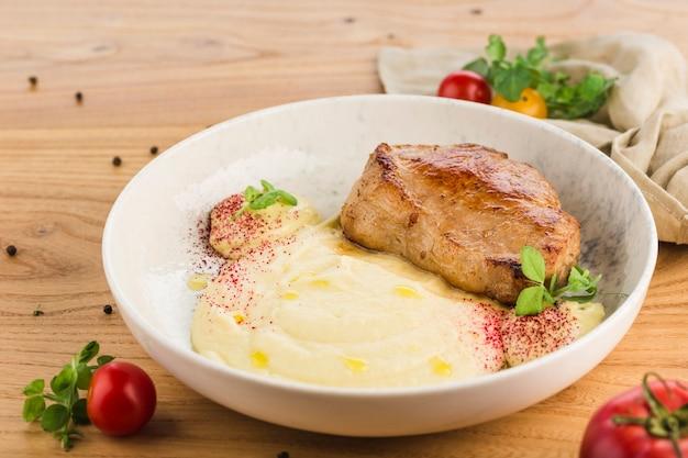 Стейк из свинины с картофельным пюре в тарелке на светлой деревянной поверхности.