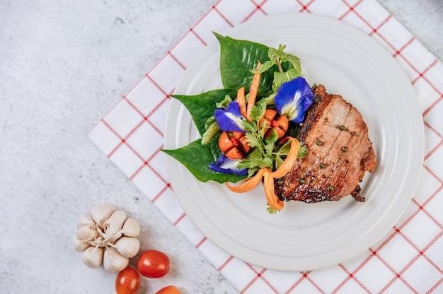 Bistecca di maiale con pomodoro, carota, cipolla rossa, menta piperita, fiore di pisello farfalla e lime.