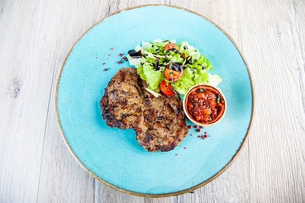 Pork steak with tomato spicy sauce and salad