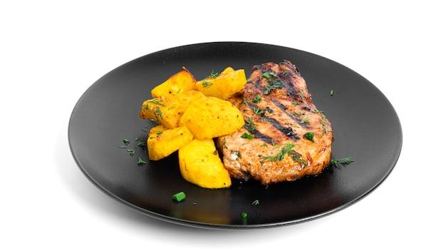 Стейки из свинины в соусе и печеный картофель на изолированной тарелке.