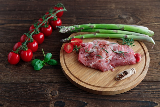 Pork steaks lie on a round cutting board next to fresh green asparagus and cherry tomatoes