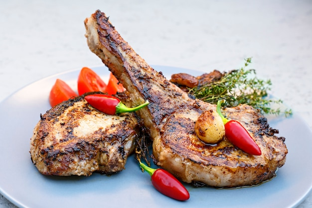 Pork steaks on a plate with chili, tomatoes