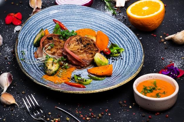 Медальоны из свиной вырезки в беконе с острым соусом и брюссельской капустой, на темной поверхности