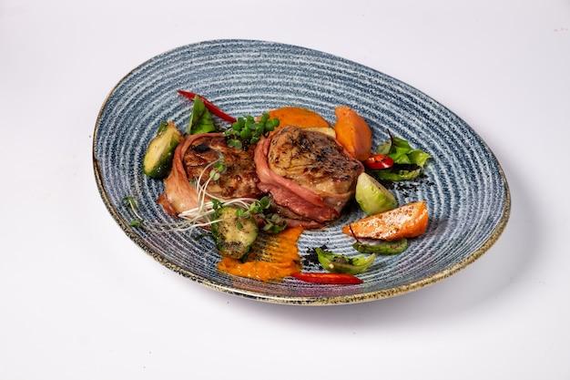 Медальоны из свиной вырезки в беконе с острым соусом и брюссельской капустой, на белой поверхности