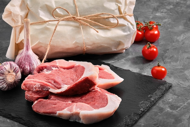 Pork tenderloin two pieces of pork meat on a slate plate on a gray background copy space photo for grocery stores