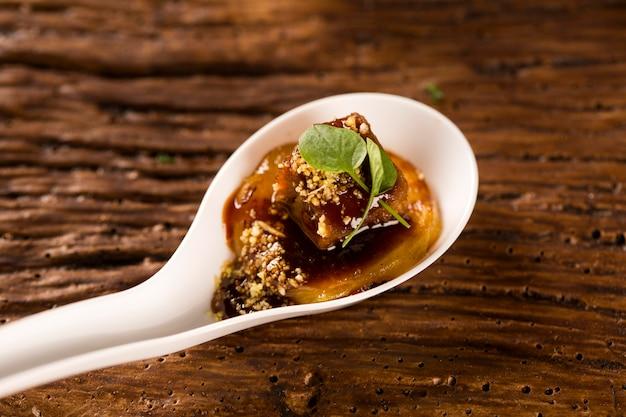 Свиной язык, молотый банан, марсала, водяная мука и мини-кресс-салат в ложке. вкус гастрономической еды руками