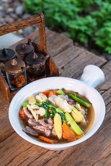 ケール、ニンジン、卵をトッピングしたポーク、おいしい、付け合わせ、木製のテーブルの上に置かれた美しいテラコッタカップに入れられます。