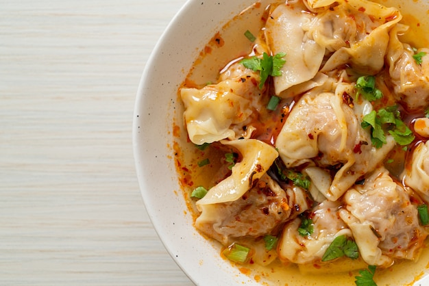 Pork wonton soup or pork dumplings soup with roasted chili - asian food style