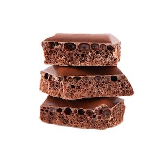 다공성 초콜릿 조각 흰색 배경에 고립입니다. 블랙 화난 초콜릿.