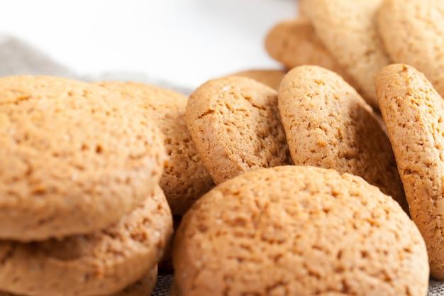 Пористое печенье, запеченное с овсянкой, не очень сладкое сухое и хрустящее печенье, крупный план - не очень калорийное овсяное печенье.
