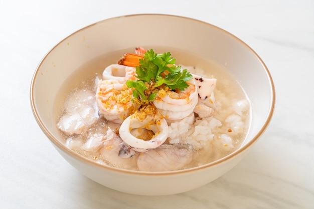 해물 (새우, 오징어, 생선) 사발을 곁들인 죽 또는 삶은 쌀국