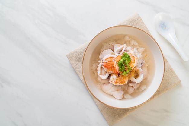 お粥またはご飯とシーフード(エビ、イカ、魚)のボウル