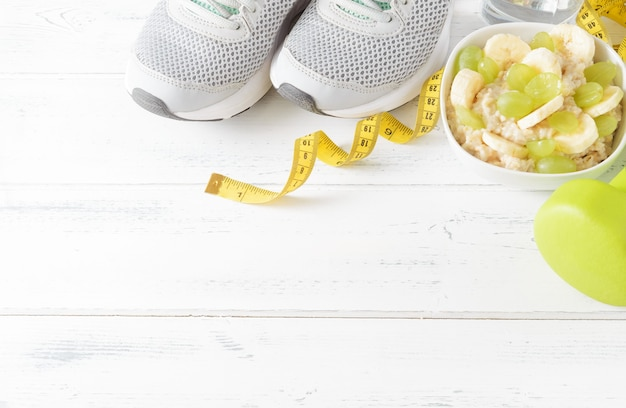 Porridge with grapes , banana slices , green dumbbells, sneakers, measuring tape on a white wooden surface top view