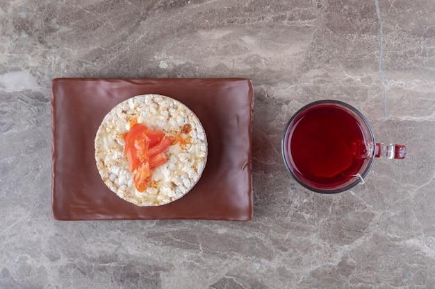 Каша с ломтиками помидора в стакане на деревянной тарелке, на мраморном фоне.