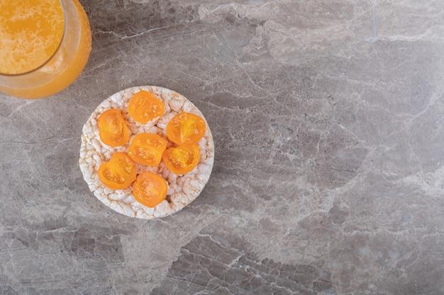 大理石の表面にあるオレンジジュースの隣にあるグラスにトマトのスライスが入ったお粥