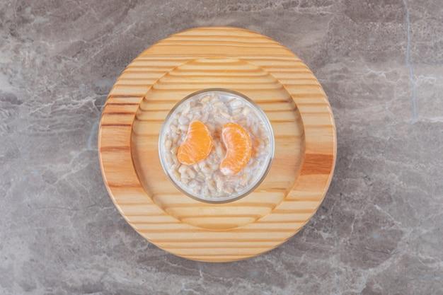 Каша с двумя дольками апельсина в стакане на деревянной тарелке, на мраморном фоне.