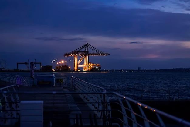 夜の距離で船を積み込むコンテナターミナルのポートクレーン