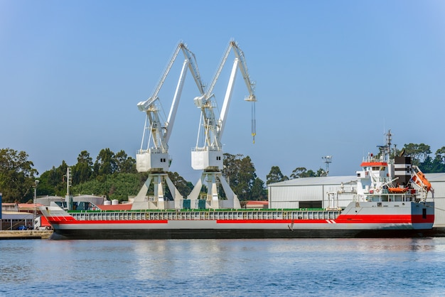 Port cranes loading industrial cargo ship in seaport