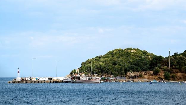 桟橋の近くに係留されたボートがあるエーゲ海沿岸のオリンピアダ港