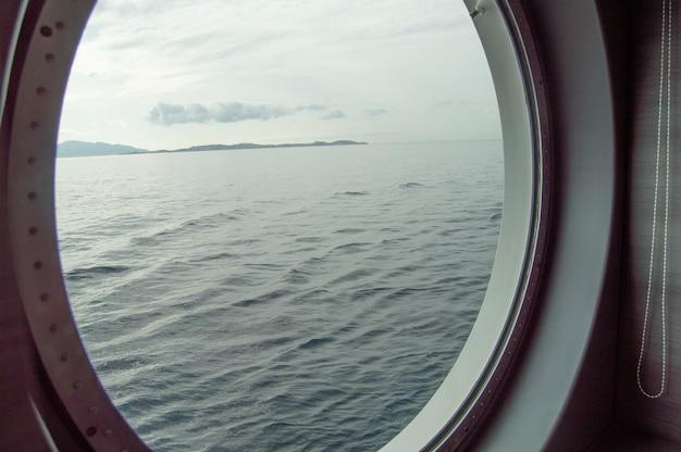 クルーズ船の丸いport窓、海岸と海の窓からの内部ビュー、海に対する日の出、クローズアップ