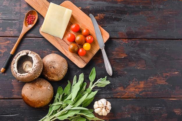 Portabello 버섯 베이킹 재료, 체 다 치즈, 체리 토마토와 세이 지 오래 된 어두운 테이블, 텍스트에 대 한 상위 뷰 공간에 버섯.