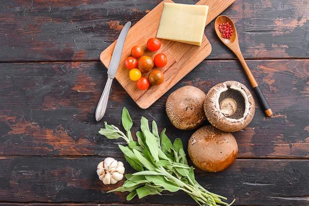 오래 된 어두운 나무 테이블에 제빵, 체다 치즈, 체리 토마토 및 세이지, 상위 뷰를위한 portabello 버섯 재료