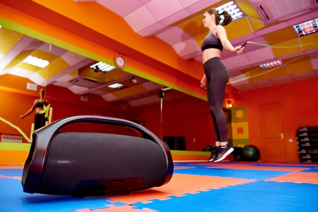 Портативная акустика в зале аэробики на фоне размытой девушки на кардио тренировке.