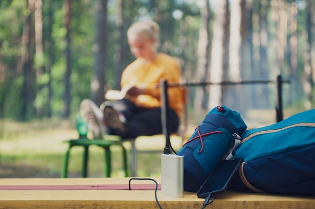 Portable charger in camping. girl tourist reading a book in the woods on the background of a backpack and bank turn.