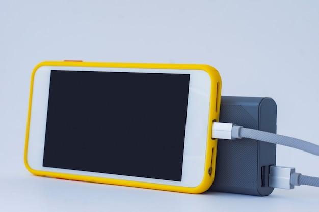 ポータブル充電器は、白い背景で隔離されたスマートフォンを充電します。白い画面とパワーバンクを備えた携帯電話のモックアップ。